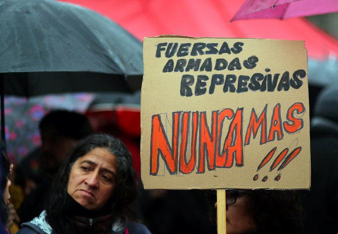 """Durante una protesta en la Plaza de Mayo el 26 de julio de 2018, una mujer sostiene un cartel con la frase emblemática de la Argentina posdictadura: """"Nunca más"""". Credit Marcos Brindicci/Reuters"""